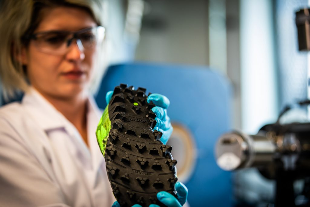 female scientist inspecting a hiking shoe in a lab